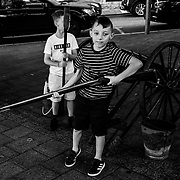 Children play with a canon and rifle during Loyalist reenactment demonstrations a day before a Loyalist parade as the Apprentice Boys of Derry will later initiate new members. Northern Ireland, September 2019