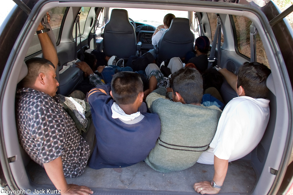 05 MAY 2003 -- SELLS, AZ:  A group of 11 undocumented immigrants from Mexico wait for the Border Patrol in the back of a mini-van west of Sells, AZ, the capital of Tohono OOdham Indian Reservation, May 5, 2003. The van was stopped for a traffic violation by the tribal police, who found the immigrants hiding in the van. The driver of the van was arrested for driving without a license, no insurance and having false license plates. The Tohono O'Odham reservation covers a vast expanse of Southern Arizona and has a 70 mile border with Mexico. In recent years the reservation has been flooded with undocumented immigrants who pass through the reservation on their way north to Phoenix, AZ, and other cities in the US. About 1,500 undocumented immigrants, most from Mexico, cross the reservation, which has more land than the state of Delaware,  every day. According to the tribal government, the tribal police department spends about 60 percent of its resources dealing with crime created by the undocumented immigrants. Many times tribal police officers have to wait hours for the US Border Patrol to respond to calls to pick up undocumented immigrants. The officer waited for more than an hour for Border Patrol to arrive on the scene and eventually released the immigrants. Border Patrol arrived minutes later and apprehended all of the immigrants.   PHOTO BY JACK KURTZ
