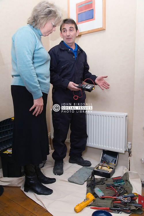 Gas man explaining to a customer what work he needs to do to fix a radiator,