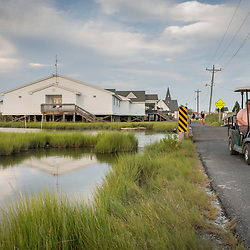 August 4, 2017 - Tangier Island, VA - The new Tangier Combined School, built on stilts near the Big Gut Canal, already has flooding underneath its supports.  Here a couple on a golf cart, the island's dominant mode of transportation cruise over one of the many small bridges that connect the island which is striated by waterways.<br />  Photo by Susana Raab/Institute