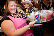 Waitress smiling with bottled beer in her shirt while serving at the Save A Sister Bachelor Auction at the Blue Moon Nite Club in Columbia Falls, Montana.