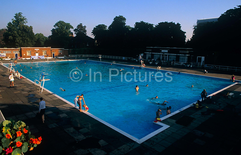Seen from the roof, we see an aerial perspective of an early morning swim for many south London locals as they bathe in the unheated pool of  the Grade II listed  Brockwell (Brixton) Lido in Brockwell Park, Herne Hill. The Lido is a magnet, an oasis, for city dwellers to escape, if only for an hour from the pressures of fast urban life. Many enjoy the benefits of outdoor bathing and the friendship of meeting old friends. In the centre, a mother helps her young daughter up from the cool morning water before another hot day in August. Brockwell Lido is a large, open air swimming pool in Brockwell Park, Herne Hill, London. It opened in July 1937, closed in 1990 and after a local campaign was re-opened in 1994. Brockwell Lido was designed by HA Rowbotham and TL Smithson of the London County Council's Parks Department to replace Brockwell Park bathing pond.