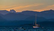 Sailboat, evening light, The Coast Range, telephoto view from Savary Island, August, Salish Sea, Sunshine Coast, British Columbia, Canada