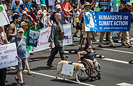 Mia Ives-Rublee and her dog Ari, from North Carolina, at the Climate March. She said that she doesn't think people realize the impacts climate change has on the disability community. Climate change exacerbates health conditions and causes stress.