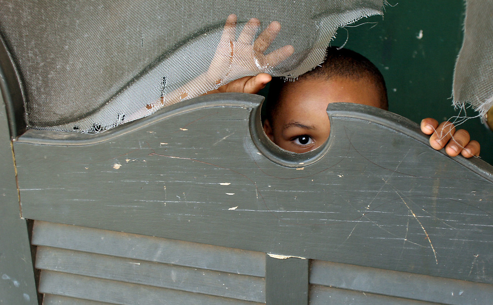 Columbia, SC. 07-20-06. C. Aluka Berry - The State.<br /> Roosevelt Village resident, Tayshaun Perry,5, peers through a screened door next to home. Tayshaun's family has lived in the village for five years and are not sure where they will be moving to. cq