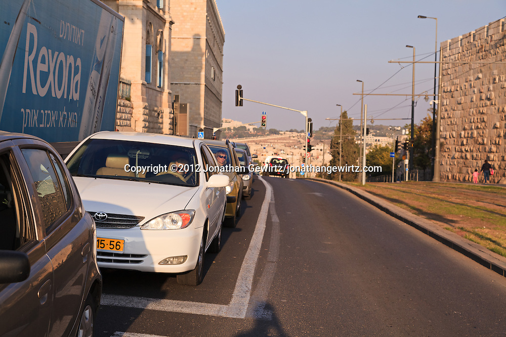 Automobile traffic on Sultan Suleiman Street in downtown Jerusalem, next to light-rail tracks and the walls of the Old City. WATERMARKS WILL NOT APPEAR ON PRINTS OR LICENSED IMAGES.