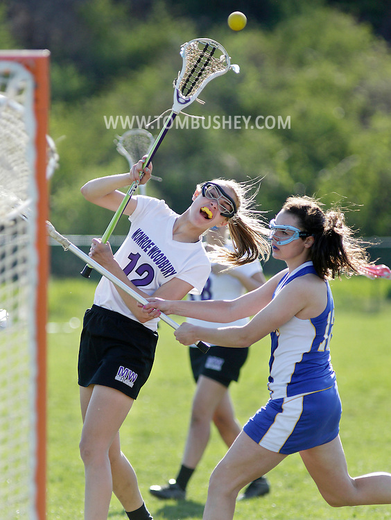 Monroe-Woodbury's McKenna Hiller, left, takes a shot as Washingtonville's Shayne Postiglione defends during a game in Central Valley on Friday, April 26, 2013. Hiller scored on the play.