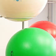 green, red, and white exercising balls on holding rack