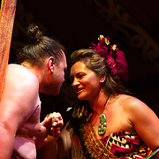 Two Maori cultural performers greet each other with a hongi, a traditional Maori greeting in New Zealand,  which is done by pressing one's nose to another person at an encounter...The traditional hongi greeting took place at the  Maori Cultural Performances at Te Puia, Maori Arts and Crafts Institute, Te Whakarewarewa Thermal Valley, Rotorua, New Zealand..Te Puia is the premier Maori cultural centre in New Zealand - a place of gushing waters, steaming vents, boiling mud pools and spectacular geysers. Te Puia also hosts National Carving and Weaving Schools and  daily maori culture performances including dancing and singing. Rotorua, 8th December 2010 New Zealand.