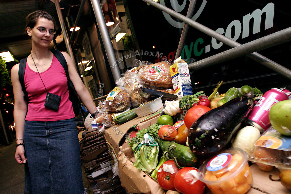 Sima, 27, member of the Freegan community in New York looking at part of the food recovered from one place only, during a Freegan trash tour to dump sites alond 3rd Avenue in Manhattan, New York, NY., on Wednesday, July 19, 2006. Freegans are a community of people who aims at recovering wasted food, books, clothing, office supplies and other items from the refuse of retail stores, frequently discarded in brand new condition. They recover goods not for profit, but to serve their own immediate needs and to share freely with others. According to a study by a USDA-commissioned study by Dr. Timothy Jones at the University of Arizona, half of all food in the United States is wasted at a cost of $100 billion dollars every year. Yet 4.4 million people in the United States alone are classified by the USDA as hungry. Global estimates place the annual rate of starvation deaths at well over 8 million. The massive waste generated in the process fills landfills and consumes land as new landfills are built. This waste stream also pollutes the environment, damages public health as landfills chemicals leak into the ground, and incinerators spew heavy metals back into the atmosphere. Freegans practice strategies for everyday living based on sharing resources, minimizing the detrimental impact of our consumption, and reducing and recovering waste and independence from the profit-driven economy. They are dismayed by the social and ecological costs of an economic model where only profit is valued, at the expense of the environment. In a society that worships competition and self-interest, Freegans advocate living ethical, free, and happy lives centred around community and the notion that a healthy society must function on interdependence. Freegans also believe that people have a right and responsibility to take back control of their time.