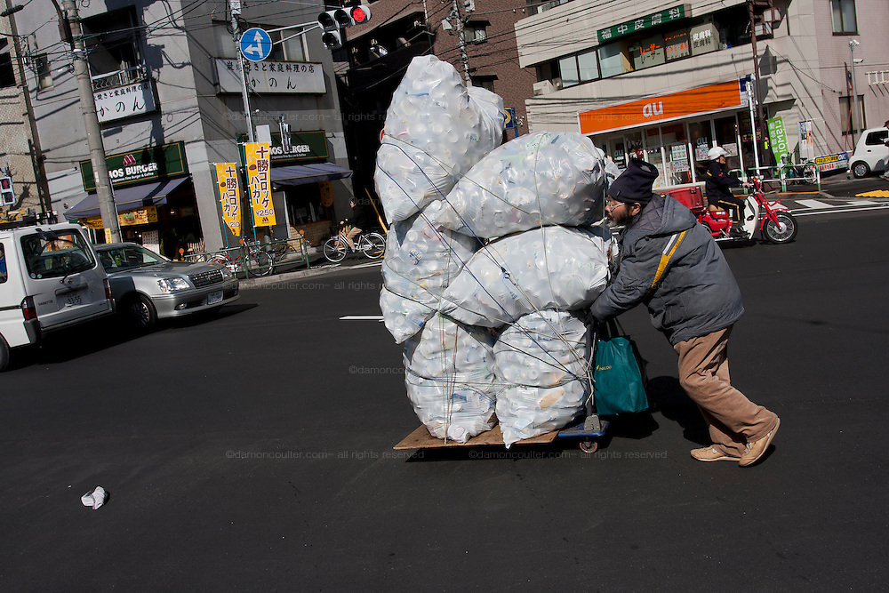 A homeless man collects tin cans to sell for recycling. Tokyo, Japan. Saturday, March 7th 2009