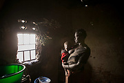 Harriet stands with one-year-old son, Sahidi, in her home in Gulu. Harriet was abducted by LRA at the age of eight in Wiiagwem village in Lira District, and spent 13 years in the bush as a girl soldier and a sex slave. she said her husband, a captain in charge, had four wives. She gave birth to two children in the bush and later had six more from the new husband. The new husband rarely stays with her. She sells boiled corns to support herself and children.