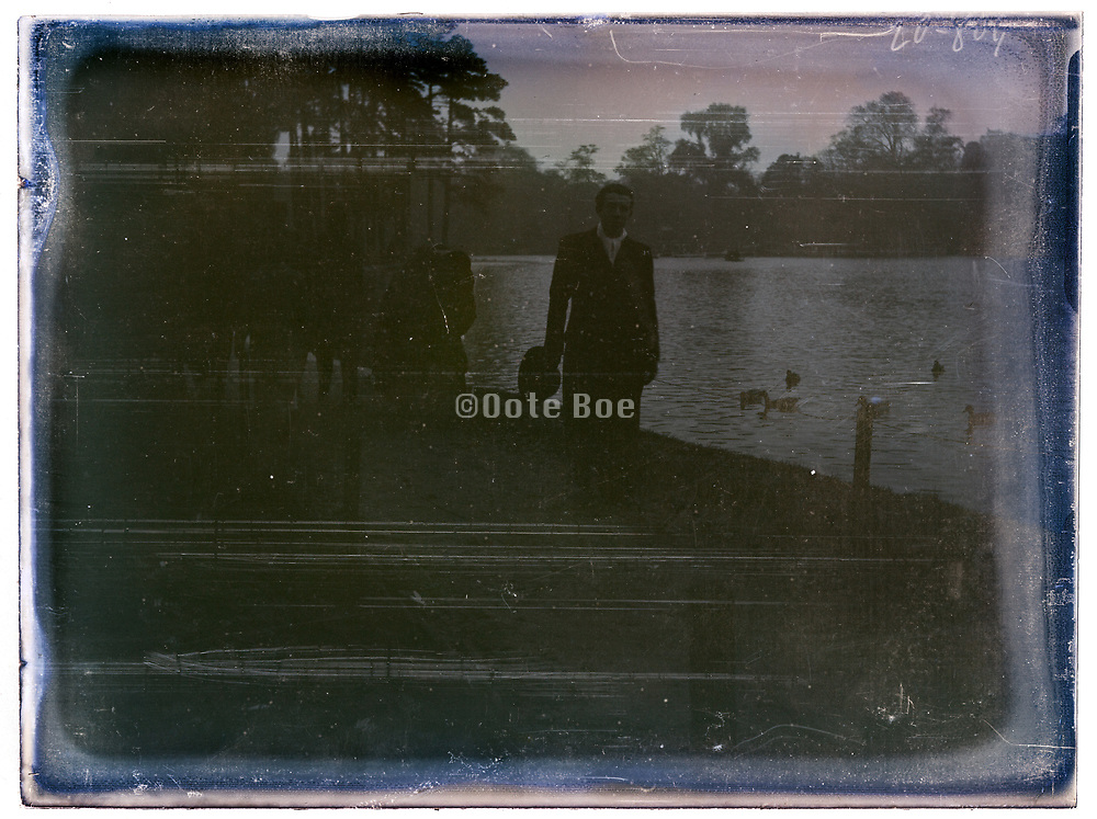 deteriorating glass plate of man standing by a park lake France 1920s 1930s