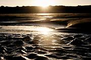 Small waves on the beach due to the changing of the tide in the morning sun.   Kleine golfjes aan het strand door wisseling van getijde in de ochtedzon.