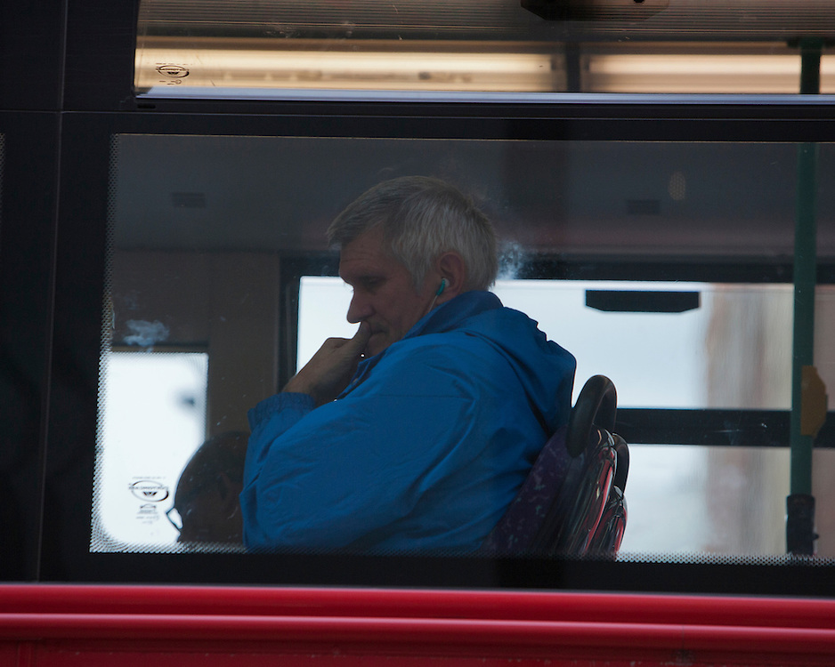 Man on a London bus listening to music
