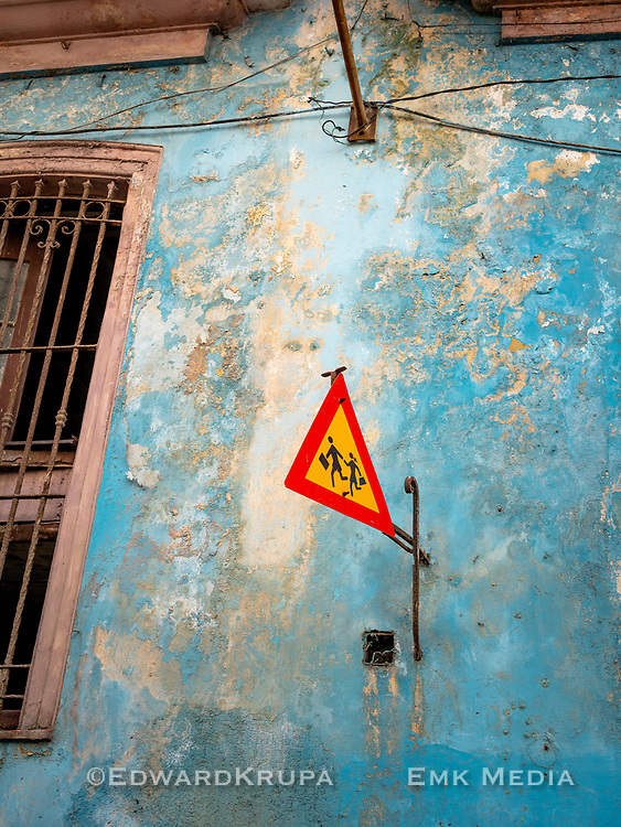 Watch out for school children! safety sign,  hanging on the weathered blue wall of a school  building in Old Havana.