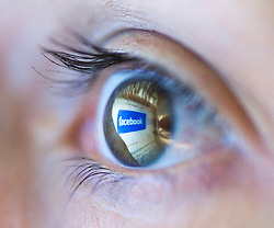 Facebook logo on computer screen reflected in womans eye