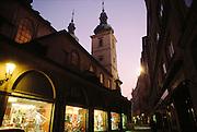 Prague, Czech Republic. Old town street at dusk with lighted shop windows.