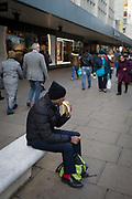 A man rests in the street to eat a banana, on 22nd November 2017, in Oxford Street, London England.