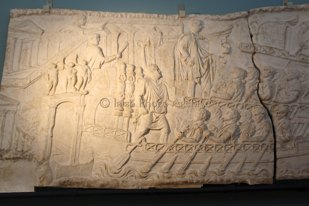 Departure from Ancona.  Trajan's column, Rome, AD 113.  Trajan's fleet leaves from Ancona at night.  The emperor stands in a ship and addresses his troops; a lantern hangs at his right.  High waves and dolphins represent the open sea, while buildings, columns and arches set the scene in the harbour city.