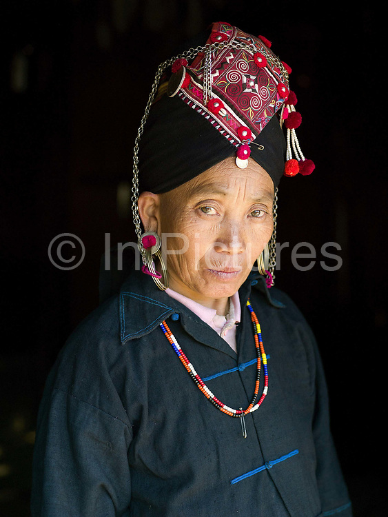 Portrait of an Akha Oma ethnic minority woman wearing her traditional clothing; Ban Sala Aebe, Phongsaly Province, Lao PDR. The Oma are one of Laos' smallest ethnic groups with only a few villages in Phongsaly Province. Cotton growers, indigo dyers and exquisite embroiderers result in traditional clothing being both colourful and unique. One of the most ethnically diverse countries in Southeast Asia, Laos has 49 officially recognised ethnic groups although there are many more self-identified and sub groups. These groups are distinguished by their own customs, beliefs and rituals. Details down to the embroidery on a shirt, the colour of the trim and the type of skirt all help signify the wearer's ethnic and clan affiliations.