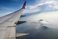 View from the window on a Lion Air commercial airplane flying over volcanic landscape on the Indonesian island of Java.
