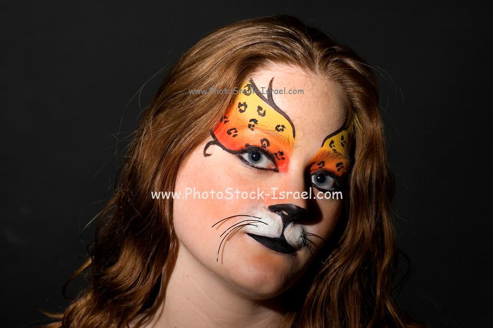 young teenage female model with elaborate tiger make up mask on black background model released studio shot