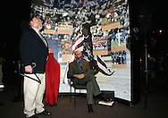 Will Lunn (seated), president of the Hall of Fame, and Director of Communications Jack Huckel (left, holding a Hall of Fame jacket) wait in the wings for an inductee on Monday, August 29, 2005, during the 2005 National Soccer Hall of Fame Induction Ceremony in Oneonta, New York.