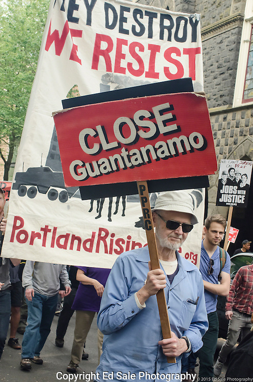 Demonstrator in 2015 May Day rally and march in Portland, Oregon holds a sign saying Close Guantanamo