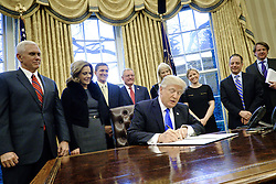 January 28, 2017 - Washington, District of Columbia, U.S. - President Donald Trump signs three executive actions in the Oval Office.The actions outline a reorganization of the National Security Council, implement a five year lobbying ban on administration officials and a lifetime ban on administration officials lobbying for a foreign country and calls on military leaders to present a report to the president in 30 days that outlines a strategy for defeating ISIS. (Credit Image: © Pete Marovich/CNP via ZUMA Wire)