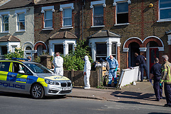 © Licensed to London News Pictures. 25/04/2020. London, UK. Forensic investigators stand next to a  police vehicle as fire fighters look on at the scene of a fatal house fire. A man has died in a house fire in Earlsfield, Wandsworth. Firefighters found the man in a ground floor bedroom. He was brought out of the property by fire crews but he died at the scene. London Fire Brigade was called at 07:36 BST and the fire was under control by 08:33 BST. Photo credit: Peter Manning/LNP