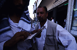 Kabul, 15 August 2005..Undercover Police (?), wearing a traditional Salwar Chemise and an automatic pistol, checking  the passport of suspects on the street.