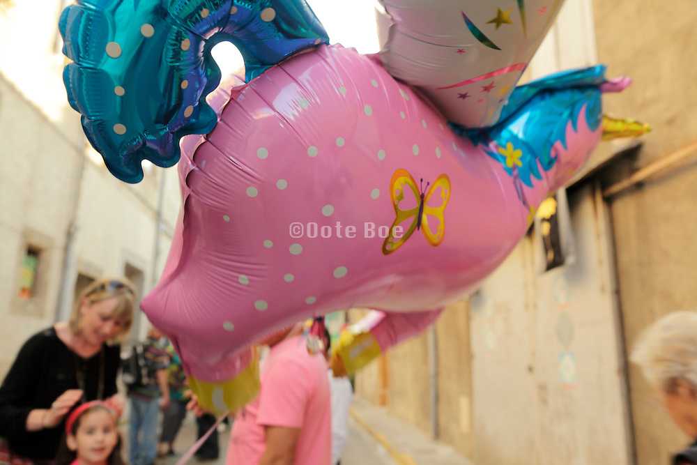 mother with child holding a pink horse with wings helium balloon