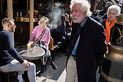 On the day that the UK government eased Covid restrictions to allow non-essential businesses such as shops, pubs, bars, gyms and hairdressers to re-open, elderly people walk past customers enjoying outdoor drinks on Old Compton Street in Soho, on 12th April 2021, in London, England.