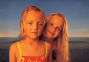 Two sisters stand together while playing on a beach during their summer vacation.