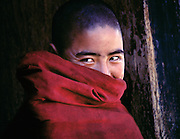 A young Buddhist monk smiles with his eyes at Paro Dzong, in the Himalayan kingdom of Bhutan.