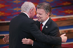 Colombia's president Juan Manuel Santos (right) hugs Northern Ireland Deputy First Minister Martin McGuinness after he addressed business leaders during a business and civic lunch at Titanic Belfast.