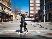 "29 MARCH 2020 - DES MOINES, IOWA: A couple crosses an empty street in downtown Des Moines. On Sunday morning, 29 March, Iowa reported 336 confirmed cases of the Novel Coronavirus (SARS-CoV-2) and COVID-19. There have been four deaths attributed to COVID-19 in Iowa. Restaurants, bars, movie theaters, places that draw crowds are closed until 07 April. The Governor has not ordered ""shelter in place""  but several Mayors, including the Mayor of Des Moines, have asked residents to stay in their homes for all but the essential needs. People are being encouraged to practice ""social distancing"" and many businesses are requiring or encouraging employees to telecommute.        PHOTO BY JACK KURTZ"