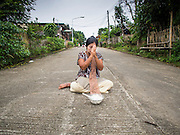 16 SEPTEMBER 2014 - SANGKHLA BURI, KANCHANABURI, THAILAND: A Burmese Mon woman sits in the road and prays before making merit and present Mon Buddhist monks with food during the morning alms round in the Mon community in Sangkhla Buri. The Mon were some of the first people to settle in Southeast Asia, and were responsible for the spread of Theravada Buddhism in Thailand and  Indochina. The Mon homeland is in southwestern Thailand and southeastern Myanmar (Burma). The Mon in Thailand traditionally allied themselves with the Thais during the frequent wars between Burmese and Siamese Empires in the 16th - 19th centuries and the Mon in Thailand have been assimilated into Thai culture. The Mon in Myanmar were persecuted by the Burmese government and many fled to Thailand. Sangkhla Buri is the center of Burmese Mon culture in Thailand because thousands of Mon came to this part of Thailand during the persecution.    PHOTO BY JACK KURTZ