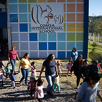 """Children arrive for school at the COMSA International School in Marcala, Honduras.<br /> <br /> Education is a core concern for the leadership and membership of the COMSA coop and the COMSA International School is a long-term initiative by the coop to improve the education of coffee farmers' children in the area. Children are accepted from the age of six months in a pre-kinder, and go up to 18 years old, before going to university. The school has had a lot of success and attention.<br /> The school questions traditional approaches to education and uses some unconventional techniques such as the Glenn Doman method. The children all learn English, French, German and Japanese.<br /> Douglas Penalba, the Glenn Doman method coordinator for the school, explained that """"the Doman method was developed to help children - including children with special needs - to develop and progress in every area, for the children to reach their fullest potential"""". Children in the school play and develop in an atmosphere of freedom, with a high teacher to student ratio, they do well academically and they are unusually successful in languages. Most children at the school study with a grant, subsidised heavily by money from Fairtrade premiums."""