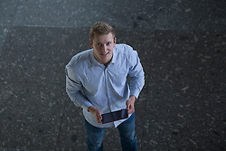 High angle view of a young man using a digital tablet, Freiburg im Breisgau, Baden-Wuerttemberg, Germany