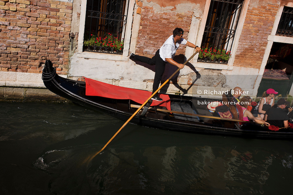 A gondolier kicks against a wall to straighten his gondola during a ride in a narrow canal in Venice, Italy. Current prices (2015) is 80 Euros for a 40-minute journey (earning them approx 130,000 Euros a year) along the waterways of this old city but rarely do gondoliers wear their straw hat.