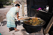 Beatrice Bautista checks on the progress of dyeing wool at her home in Teotitlan del Valle, Oaxaca state, Mexico on July 28, 2008. The Zapotec town is famous for carpet weaving, the better artists producing high quality work using natural dyes and drawing from both traditional and contemporary designs.
