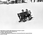 Hugo Spowers & Hubie Gibbs going down the slope on a piano during the Dangerous Sports Club Ski race. St. Moritz. 1983.<br />Film 83163f23<br />© Copyright Photograph by Dafydd Jones<br />66 Stockwell Park Rd. London SW9 0DA<br />Tel 0171 733 0108