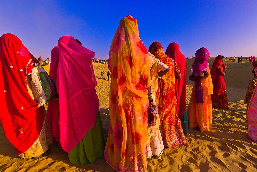 Women wearing colorful saris, Desert Festival at the Sam Sand Dunes, Thar Desert, near Jaisalmer, Rajasthan, India