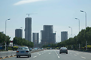 "Vehicles travel down a highway leading to the unoccupied and mostly unfinished high-rises of the Binhai New Development Zone's Yujiapu and Xiangluowan districts in Tianjin, China on 16 July 2013. The districts had the ambition of becoming China's newest financial center and dubbed by some ""the Manhattan of the East"",  however as the country tries to steer away from an investment driven economy, such projects are facing increasing scrutiny."