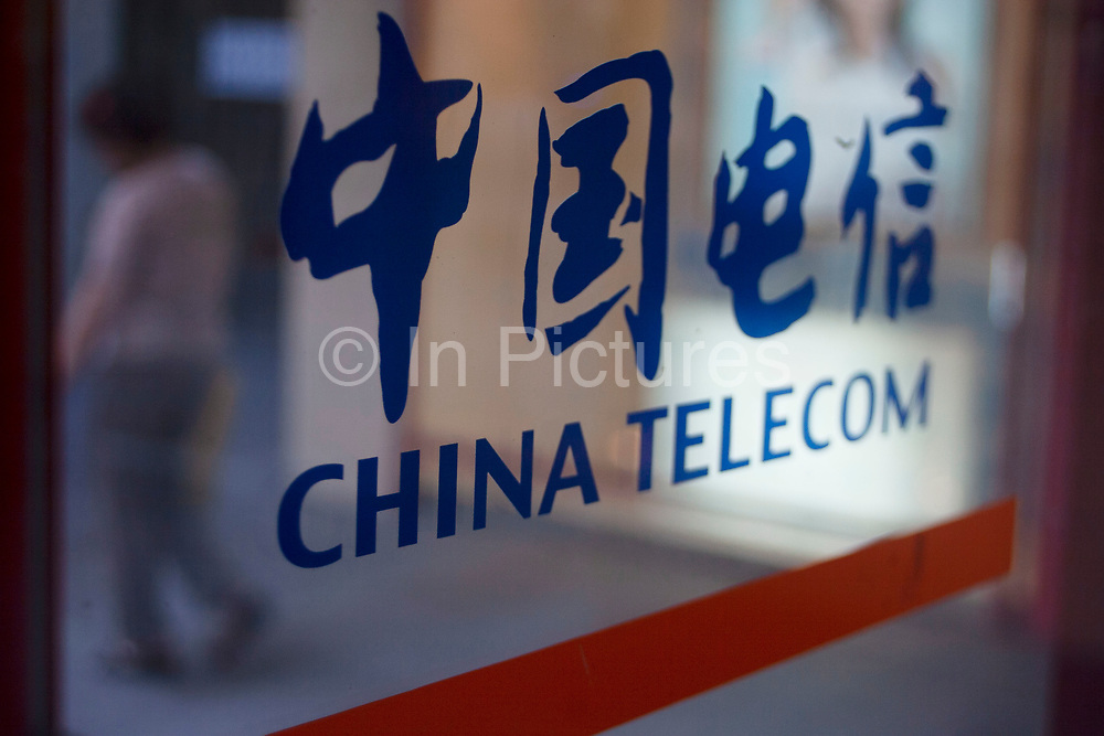 China Telecom sign on a public phone booth window on Nanjing Road. It is common for many businesses, companies or utilities to display their names in traditional Chinese characters and in English, such is the westernisation of capitalist Shanghai.