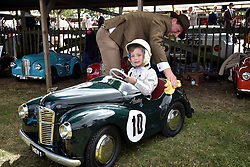 © licensed to London News Pictures. 12/09/2015<br /> Goodwood Revival Weekend, Goodwood, West Sussex. UK.<br /> The Goodwood Revival is the world's largest historic motor racing event. Competitors and enthusiasts dress in period fashions recreating the glorious days of the race circuit.<br /> Pictured  Lottie Alexander, 8 years of age in a Austin J40 peddle car, with Dad helping out.<br /> <br /> Photo credit : Ian Whittaker/LNP