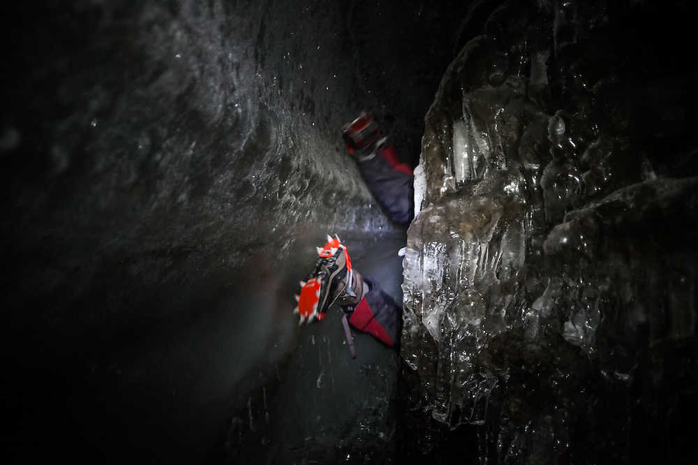 Nate Stevens climbs headfirst through a narrow passage in an ice cave in Larsbreen, Svalbard.