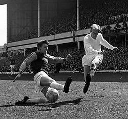 Martin Peters of West Ham United shoots out a foot in an attempt to intercept the ball as he falls in front of Manchester United's Bobby Charlton in the First Division match at Upton park.